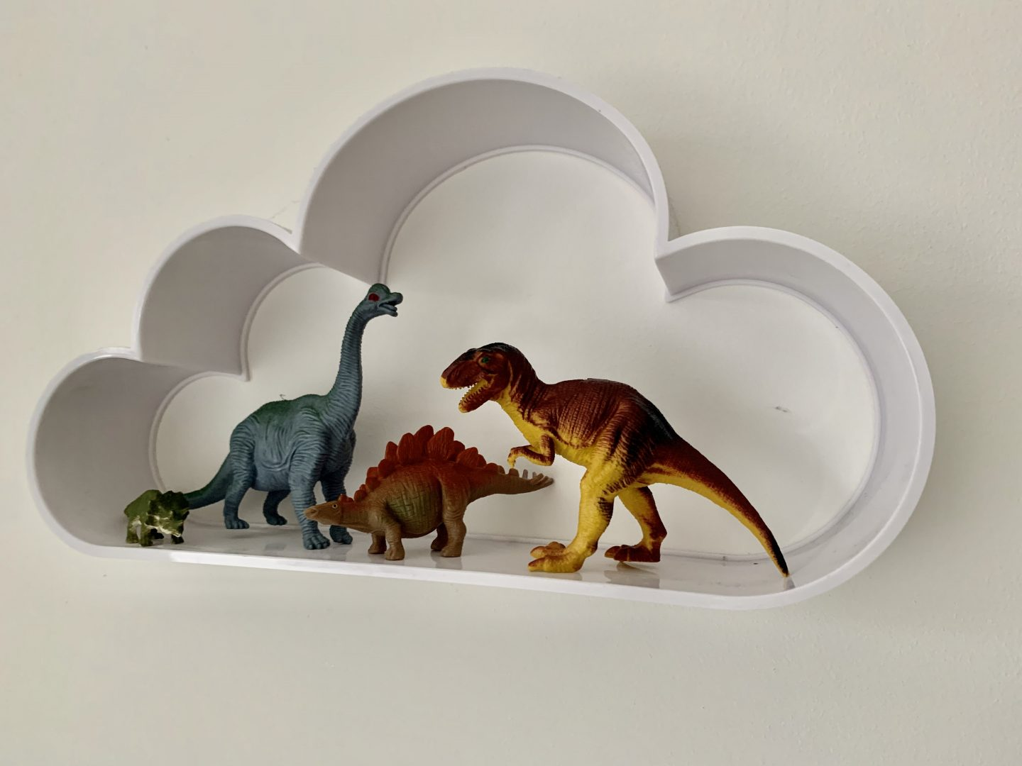 Toy dinosaurs on shelves in a dinosaur themed bedroom ideas!