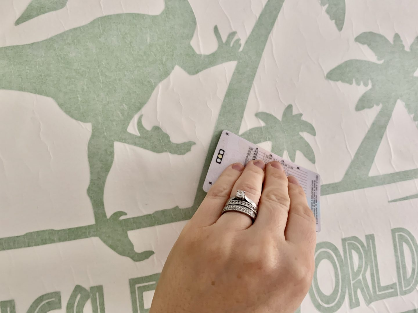 Using a credit card to transfer the wall sticker onto the wall in his dinosaur themed bedroom