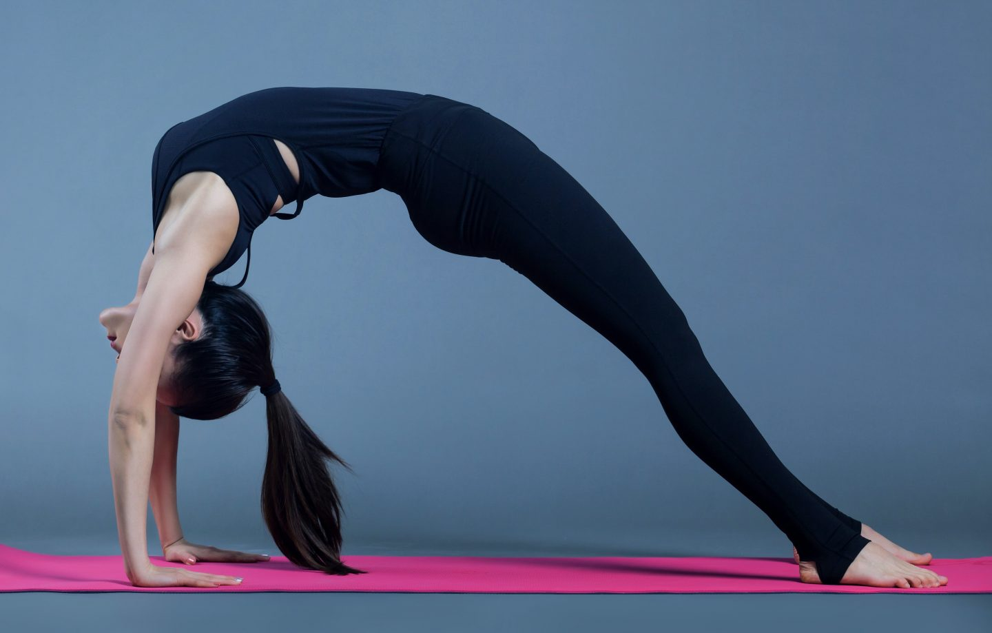 Things to buy before your first yoga class including a yoga mat - lady doing a stretch on a pink yoga mat