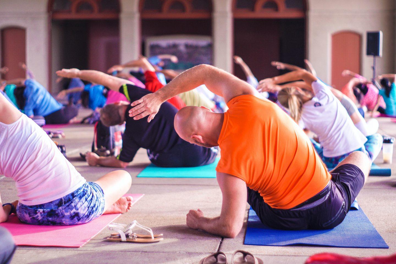 Yoga class with people doing a yoga pose on yoga mats