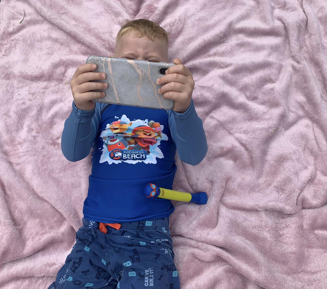 My son watching the phone whilst wearing a Kangaroo Beach rash vest